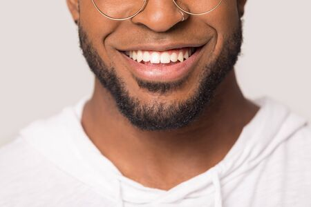 Photo pour Close up beautiful wide toothy African American male smile, healthy clear white teeth, happy black man, satisfied client, good dental service, dentistry concept, isolated on studio background - image libre de droit