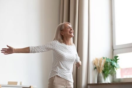 Photo pour Laughing carefree middle-aged woman standing in living room stretched hands closed eyes breathing fresh air feels happy healthy, starts new day positive mood and thoughts, dancing enjoy life concept - image libre de droit