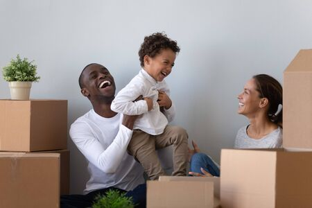 Foto de Happy laughing african american young man rising up joyful mixed race cute little son, having fun with wife. Overjoyed smiling multiracial family playing near carton packages, moving in first home. - Imagen libre de derechos