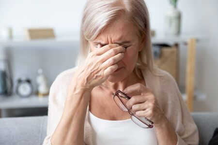 Photo pour Elderly woman crying wipes tears with hands feels unhappy, bad news. Middle-aged woman taking off glasses closed eyes rubbing eyelid suffers from eye strain deterioration eyesight with age concept - image libre de droit