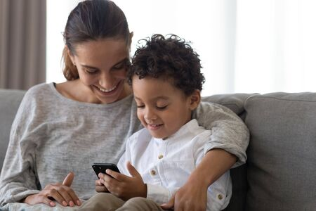 Photo for Happy young mother embracing small preschool mixed race cute kid son, sitting on couch at home together, using educational applications on smartphone, playing online games or watching funny cartoons. - Royalty Free Image
