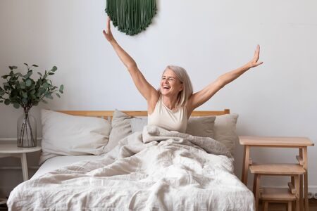 Foto de Refreshed elderly 50s female wakes up in morning stretches seated in bed in light bedroom at home, middle-aged woman feels happy and peppy after enough sleeping, greeting new day, good morning concept - Imagen libre de derechos