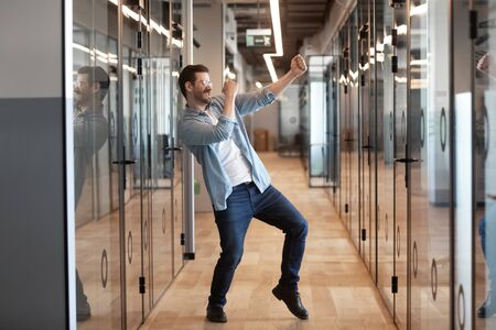 Photo pour In office hallway dancing happy worker got promotion celebrating success higher rate of pay receive financial bonus, candidate for post was hired, employee feels excited work done, its Friday concept - image libre de droit