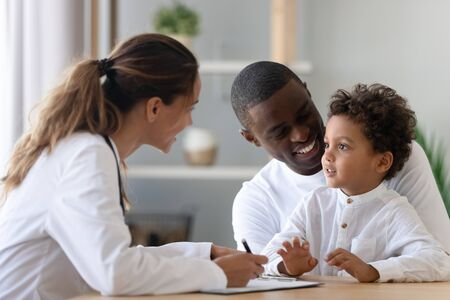 Foto de Cheerful young female pediatrician and african american smiling father listening to mixed race little patient, telling doctor about well-being. Happy multiracial family visiting clinic for check up. - Imagen libre de derechos