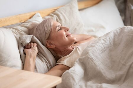 Foto de Middle-aged attractive woman lying in bed on comfortable memory foam pillow fresh beige color bed clothes enjoying early morning awakened at home closed eyes dreaming visualizing perfect day concept - Imagen libre de derechos