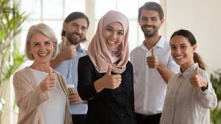 Foto de Head shot portrait of smiling successful multiracial group of younger and older business people with arabic female team leader in hijab showing thumbs up gesture, looking at camera, feeling happy. - Imagen libre de derechos