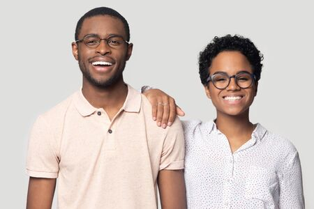 Photo pour Smiling excited african american married family couple in eyeglasses looking at camera. Young happy black woman leaning on husbands shoulder, posing for photo, isolated on grey studio background. - image libre de droit