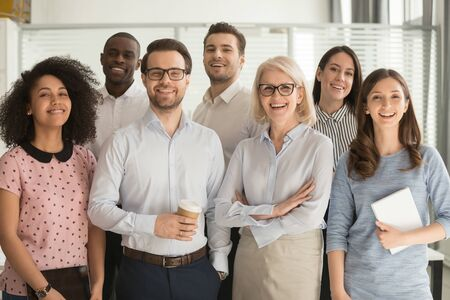 Photo pour Smiling multiethnic employees standing looking at camera making team picture in office together, happy diverse work group or department laugh posing for photo at workplace, show unity and cooperation - image libre de droit