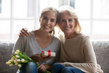 Photo for Portrait of smiling senior 50 mom and grownup daughter sit on couch look at camera hold gift box and flowers bouquet, happy elderly mother and adult child woman celebrate birthday together - Royalty Free Image