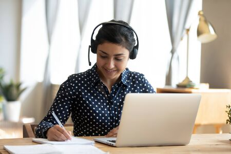 Photo pour Happy indian girl student wear headset study online with webcam teacher write notes, happy young woman listen lecture watch webinar on laptop sit at desk, distance e learn language education concept - image libre de droit