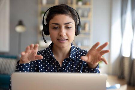 Foto de Indian young business woman student teacher tutor wear wireless headset video conference calling on laptop computer talk by webcam learn teach in online chat, distance webinar online teaching concept - Imagen libre de derechos