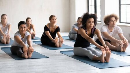 Photo pour Diverse people with African American female instructor doing Seated forward bend exercise, practicing yoga at group lesson, stretching in paschimottanasana pose, working out in modern yoga center - image libre de droit