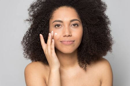 Photo pour Head shot close up portrait pleasant happy african american young lady applying moisturizing cream balm on skin. Attractive mixed race girl grooming herself isolated on gray studio background. - image libre de droit