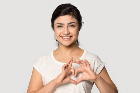 Photo pour Head shot studio close up portrait smiling happy young indian ethnicity woman making heart shape gesture symbol, demonstrating love, kindness, tender romantic feelings isolated on grey background. - image libre de droit