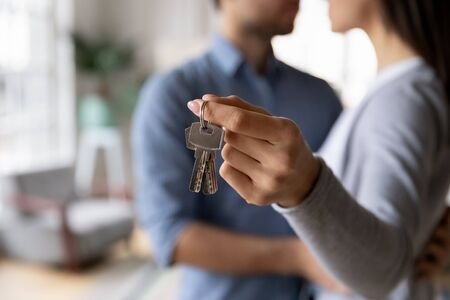 Close up of young couple hug at new home hold house keys moving in together, loving caring husband and wife apartment owners excited relocating to own dwelling, renting, relocation concept
