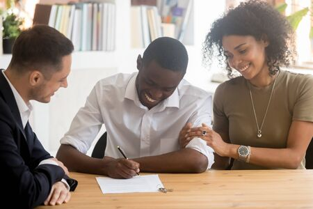 Photo pour Happy black millennial couple sign contract closing deal with real estate agent buying home together, excited african American husband put signature on agreement rent take loan with wife at broker - image libre de droit
