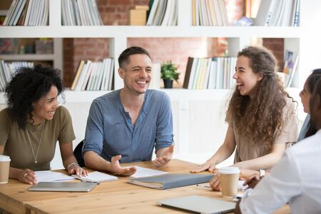 Photo pour Happy multiracial millennial people sit at shared office desk laugh joking at casual team meeting, smiling diverse colleagues have fun talking chatting at work briefing. Cooperation, teamwork concept - image libre de droit