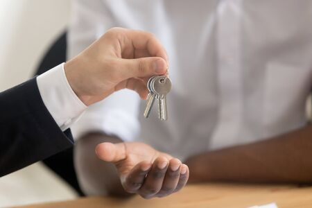 Close up of real estate agent hold give keys to african American buyer closing deal buying home, realtor or broker make agreement with black customer renting apartment or become property owner