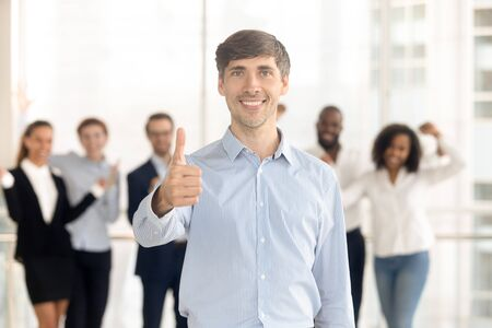 Photo pour Happy Caucasian man employee or leader stand front show thumbs up recommending company service, smiling male client look at camera give recommendation, excited team support motivate at background - image libre de droit