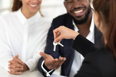 Photo pour Close up of female realtor or real estate agent give house keys to excited multiethnic young married couple, woman broker greeting happy spouses become property owners, buying first home together - image libre de droit