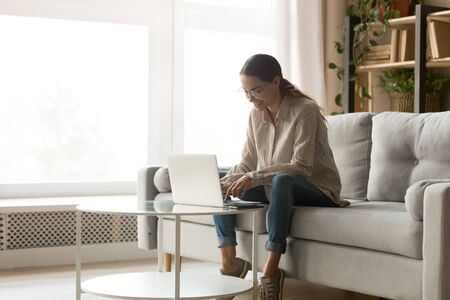 Photo for Young happy smiling mixed race woman working with computer in living room, chatting with friends, dating online, shopping, writing blog. Millennial motivated student studying, preparing for exam. - Royalty Free Image