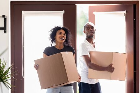 Photo pour Excited young black couple hold cardboard boxes entering own house for first time, happy African American man and woman carrying packages impressed moving in new home. New beginning concept - image libre de droit