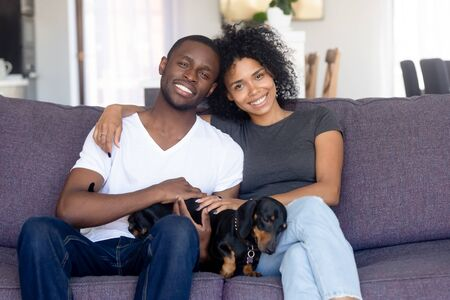 Photo pour Portrait of happy African American couple hug sitting on couch with cute dog, smiling black husband and wife pose with dackel, relaxing together on sofa, young family with pet rest in own living room - image libre de droit