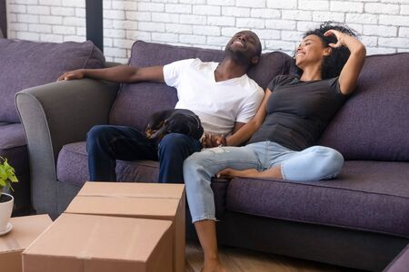 Photo pour Happy young African American couple rest on cozy couch together with favorite pet companion, have break relocating to new home, excited black family with dog relax on sofa glad to move in own house - image libre de droit