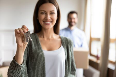 Happy young woman stand hold house keys moving in with husband to new home, excited female renter or tenant feel overjoyed relocating to own dwelling, real estate, tenancy, ownership concept