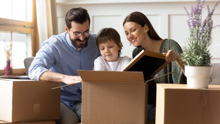 Photo pour Happy young caucasian family with little preschooler kid sit on couch unpack cardboard boxes moving to own house together, excited parents with small cute son settle at new home, relocation concept - image libre de droit