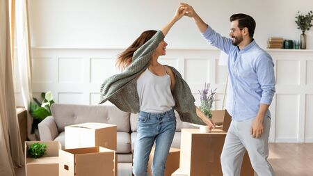 Photo pour Overjoyed young couple dance in living room near cardboard boxes entertain on moving day, happy husband and wife have fun swirl sway relocating to own apartment together, relocation concept - image libre de droit