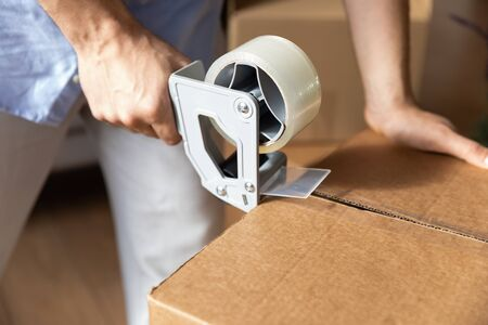 Photo pour Close up of male renter or tenant packing personal belongings use scotch in carton parcels moving to new home, man hold tape dispenser seal cardboard box package relocating, delivery service concept - image libre de droit