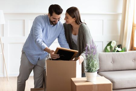 Photo pour Happy young couple feel excited unpack cardboard boxes in living room settle in new home, smiling husband and wife renters open personal belongings packages moving in together, relocation concept - image libre de droit