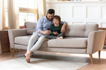 Photo pour Caring young dad sit relax on couch in living room with little preschooler son watch funny video on cellphone together, smiling father rest on sofa have fun play use smartphone with small boy child - image libre de droit