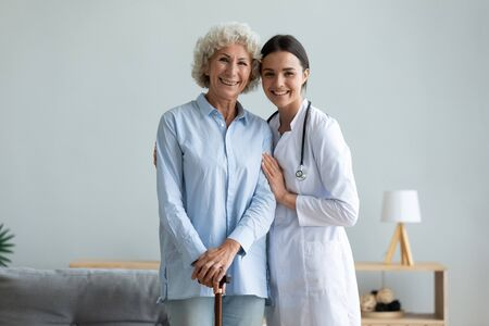 Photo pour Portrait smiling caregiver and older woman with walking cane standing at home, caring doctor wearing white uniform coat hugging, supporting mature female patient, looking at camera, healthcare - image libre de droit