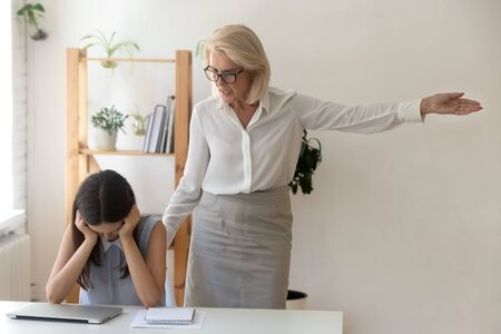 Photo pour Angry female boss dismissing frustrated girl subordinate, annoyed employer telling unprofessional employee to get out pointing with hand to door fired from job, losing work, becoming jobless concept - image libre de droit
