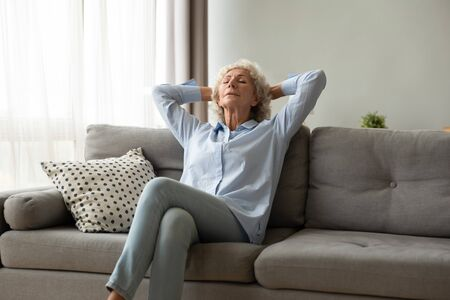 Photo for Peaceful older woman sitting, sleeping on comfortable couch, relaxing with hands behind head at home, day dreaming, calm mature female with closed eyes enjoying free time leaning back, meditating - Royalty Free Image