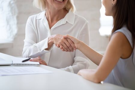 Foto für Close up view middle-aged businesswoman boss and millennial female applicant shaking hands starting job interview seated at office desk, client and manager finished successful negotiations concept - Lizenzfreies Bild