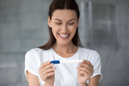 Head shot happy young woman holding pregnancy test kit, looking at result, feeling positive, excited female celebrating good news, checking planning pregnancy, fertility maternity concept