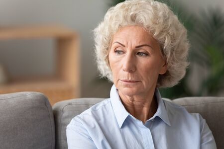 Photo for Head shot close up older woman lost in thoughts, looking to aside, sitting on couch at home alone, pensive mature female thinking about problem, nostalgia and melancholy, feeling lonely - Royalty Free Image