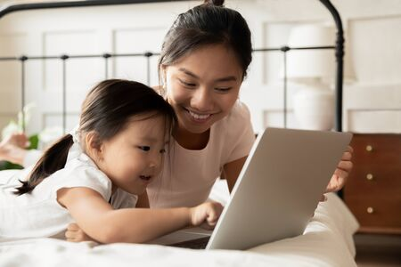 Foto de Happy young Asian mom and little ethnic daughter lying in bed at home watch video on modern laptop, smiling Vietnamese mother or nanny relax in bedroom with small biracial girl child using computer - Imagen libre de derechos
