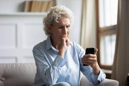 Photo pour Thoughtful middle aged hoary woman sitting on couch, holding smartphone in hands, reading news. Pensive older woman worrying about bank loan debt sms notification, thinking of financial problems. - image libre de droit