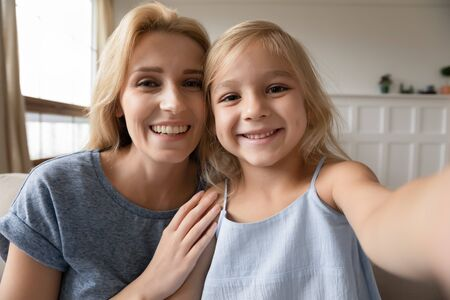 Photo pour Web cam view adorable little preschool girl making selfie with attractive young mother at home. Smiling blonde woman posing for photo ore recording funny cute video with small kid daughter indoors. - image libre de droit