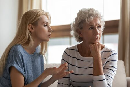 Irritated young woman asserting opinion to offended middle aged mother at home. Annoyed blonde grown up daughter arguing with stubborn mature elderly mom, two generations family disagreements concept.