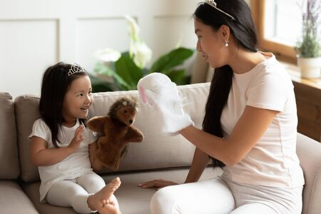 Photo pour Overjoyed young Vietnamese mum or nanny sit on couch relax play toys with little ethnic girl child, happy millennial mother or sister have fun with small Asian daughter at home, engaged in funny game - image libre de droit
