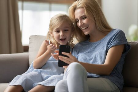 Photo pour Cute little preschool kid girl amazed by funny mobile game, enjoying spending time together with blonde mother. Smiling attractive young woman showing interesting apps to curios small daughter. - image libre de droit