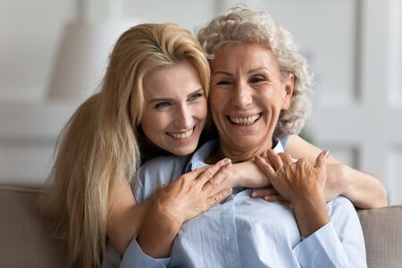 Photo pour Attractive smiling young blonde woman embracing from back sitting on couch older pleasant mommy. Loving two female generations family showing support care, enjoy tender sweet moment at home. - image libre de droit