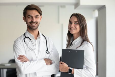Photo pour Portrait of happy Caucasian female holding clipboard and male doctor with stethoscope on shoulders wearing white coat uniform posing indoors, healthcare, medical team, successful practitioners concept - image libre de droit