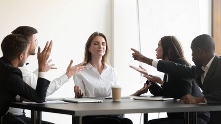 Photo pour Businesspeople sit at desk, while stressed colleagues accusing screaming express negative emotion to young businesswoman she meditating looking serene and calm, no stress anxiety at workplace concept - image libre de droit