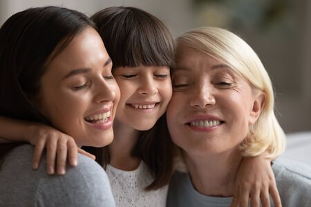 Photo pour Close up of smiling three generations of women hug and cuddle having close intimate together, happy little girl, mother and grandmother embrace touch cheeks show love and care, bonding concept - image libre de droit